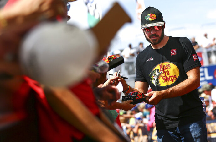 Martin Truex Jr. gives autographs to fans before a NASCAR Cup Series auto race at Las Vegas Motor Speedway, Sunday, Sept. 15, 2019. (AP Photo/Chase Stevens)