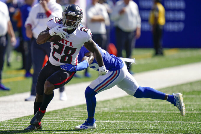 Atlanta Falcons running back Mike Davis (28) runs the ball against New York Giants free safety Jabrill Peppers, right, during the first half of an NFL football game, Sunday, Sept. 26, 2021, in East Rutherford, N.J. (AP Photo/Seth Wenig)