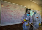 Disinfection team disinfect a classroom at Ivory Park Secondary School east of Johannesburg, South Africa, Thursday, May 28, 2020, ahead of the June 1, 2020, re-opening of Grade 7 and 12 learners to school.(AP Photo/Themba Hadebe)