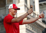 Mick Schumacher salutes Ferrari fans as they attend an event to celebrate the 90th anniversary of the foundation, at Milan's Duomo square, Italy, Wednesday, Sept. 4, 2019. The F1 GP of Italy will take place at Monza race track, near Milan, Sunday. (AP Photo/Antonio Calanni)