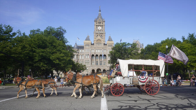 A wagon is pulled by horses during the Pioneer Day Parade Friday, July 23, 2021, in Salt Lake City. People in Utah are gathering to celebrate the state's history and recognize early Mormon pioneers who trekked West in search of religious freedom. Pioneer Day is a beloved only-in-Utah holiday every July 24 that features parades, rodeos, fireworks and more. The festivities were canceled last year because of the pandemic.(AP Photo/Rick Bowmer)