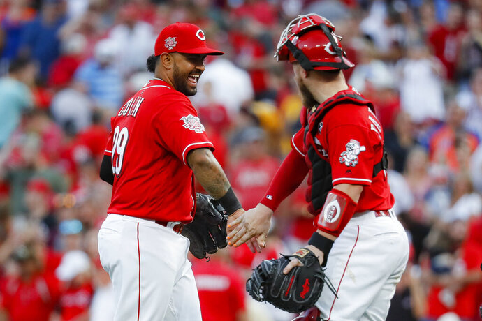Cincinnati Reds second baseman Christian Colon (29) celebrates with catcher Tucker Barnhart, right, after closing the ninth inning of a baseball game against the New York Mets, Saturday, Sept. 21, 2019, in Cincinnati. (AP Photo/John Minchillo)