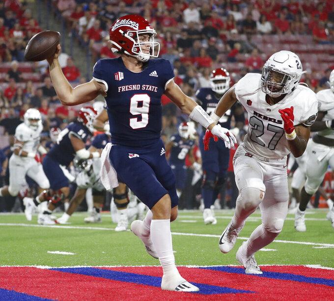 Fresno State quarterback Jake Haener avoids a sack against UNLV linebacker Austin Ajiake during the first half of an NCAA college football game in Fresno, Calif., Friday, Sept. 24, 2021. (AP Photo/Gary Kazanjian)