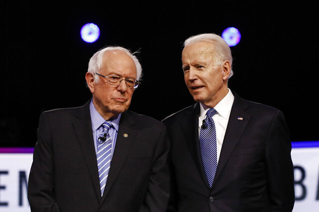 FILE - In this Feb. 25, 2020 file photo, Democratic presidential candidates, Sen. Bernie Sanders, I-Vt., left, and former Vice President Joe Biden, talk before a Democratic presidential primary debate in Charleston, S.C. Political task forces Biden formed with Sanders to solidify support among the Democratic Party's progressive wing recommended Wednesday, July 8, that the former vice president embrace proposals to combat climate change and institutional racism while expanding health care coverage and rebuilding a coronavirus-ravaged economy. (AP Photo/Matt Rourke, File)