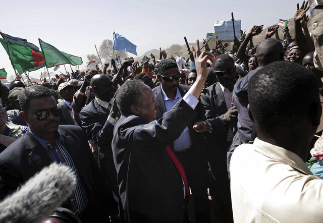 Sudanese Prime Minister Abdalla Hamdok, center, waves to people in the conflict-affected remote town of Kauda, Nuba Mountains, Sudan, Jan. 9, 2020. Hamdok, accompanied by United Nations officials, embarked on a peace mission Thursday to Kauda, a rebel stronghold, in a major step toward government efforts to end the country's long-running civil conflicts. (AP Photo/Nariman El-Mofty)