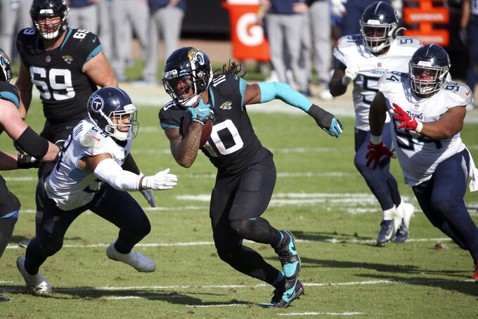 Jacksonville Jaguars wide receiver Laviska Shenault Jr. (10) runs between Tennessee Titans linebacker Harold Landry III, left, and defensive tackle Jack Crawford, right, during the first half of an NFL football game, Sunday, Dec. 13, 2020, in Jacksonville, Fla. (AP Photo/Stephen B. Morton)