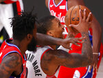 Portland Trail Blazers' Damian Lillard draws a foul from Philadelphia 76ers' Norvel Pelle, left, during the third quarter of an NBA basketball game Sunday, Aug. 9, 2020, in Lake Buena Vista, Fla. (Kevin C. Cox/Pool Photo via AP)