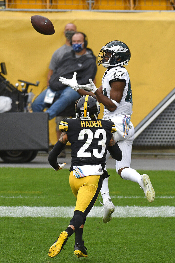 Philadelphia Eagles wide receiver Greg Ward, right, catches a touchdown pass from quarterback Carson Wentz with Pittsburgh Steelers cornerback Joe Haden, left, defending during the second half of an NFL football game in Pittsburgh, Sunday, Oct. 11, 2020. (AP Photo/Don Wright)