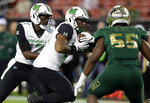 Marshall running back Anthony Anderson, center, takes the handoff from quarterback Isaiah Green, left, as he runs past South Florida linebacker Josh Black for a touchdown during the first half of the Gasparilla Bowl NCAA college football game Thursday, Dec. 20, 2018, in Tampa, Fla. (AP Photo/Chris O'Meara)