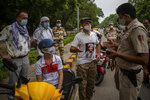 An Afghan refugee wearing a T-shirt with the picture of slain anti-Taliban fighter Ahmad Shah Massoud speaks to an Indian police officer after they were denied permission to protest outside Pakistan embassy in New Delhi, India, Thursday, Sept. 9, 2021. (AP Photo/Altaf Qadri)