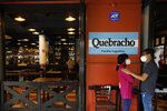 A young couple waits for their takeout order outside Argentine grill Quebracho, in the Cuauhtemoc neighborhood of Mexico City, Sunday, Jan. 10, 2021. Worried about its survival, Quebracho is one of many restaurants in the capital and adjacent Mexico State which are banning together in a campaign dubbed