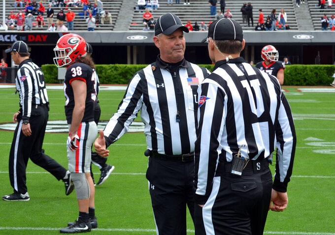 In this April 20, 2019 photo, Tom Quick talks with a colleague during Georgia's spring NCAA college football game in Athens, Ga. They're jobs have never been more difficult. Those who do it face relentless, often uninformed criticism, and attacks on their credibility. (Gary McGriff via AP)
