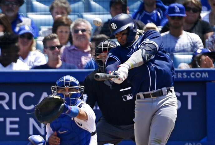 San Diego Padres' Fernando Tatis Jr., right, hits a three-run home run as Los Angeles Dodgers catcher Austin Barnes watches during the fifth inning of a baseball game Sunday, July 7, 2019, in Los Angeles. (AP Photo/Mark J. Terrill)