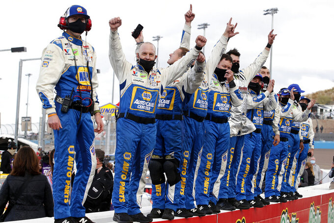 Members of Chase Elliott's pit crew stand on pit wall waiting for their driver to drive past after winning the season championship and the NASCAR Cup Series auto race at Phoenix Raceway, Sunday, Nov. 8, 2020, in Avondale, Ariz. (AP Photo/Ralph Freso)