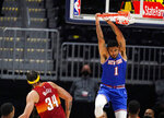 New York Knicks forward Obi Toppin, right, hangs from the rim after dunking the ball for a basket while Denver Nuggets center JaVale McGee defends in the first half of an NBA basketball game Wednesday, May 5, 2021, in Denver. (AP Photo/David Zalubowski)