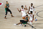 Boston Celtics' Grant Williams (12) looks on as Jayson Tatum (0) works to take a shot as Miami Heat's Derrick Jones Jr. (5), Jimmy Butler (22) and Bam Adebayo (13) defend during overtime of an NBA conference final playoff basketball game, Tuesday, Sept. 15, 2020, in Lake Buena Vista, Fla. (AP Photo/Mark J. Terrill)