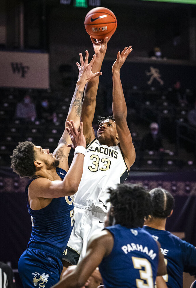 Wake Forest forward Ody Oguama (33) shoots over defense from Georgia Tech forward Rodney Howard (24) during an NCAA college basketball game Friday, March 5, 2021, in Winston-Salem, N.C. (Andrew Dye/The Winston-Salem Journal via AP)
