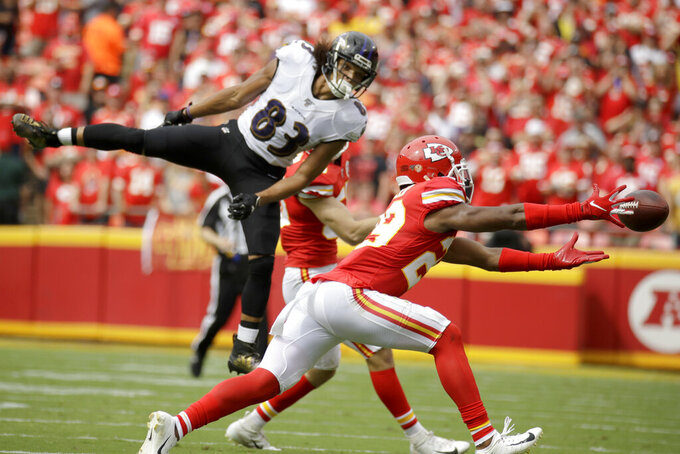 Kansas City Chiefs cornerback Kendall Fuller, right, attempts to catch the ball after Chiefs linebacker Ben Niemann, rear, broke up a pass intended for Baltimore Ravens wide receiver Willie Snead IV (83) during the first half of an NFL football game in Kansas City, Mo., Sunday, Sept. 22, 2019. (AP Photo/Charlie Riedel)