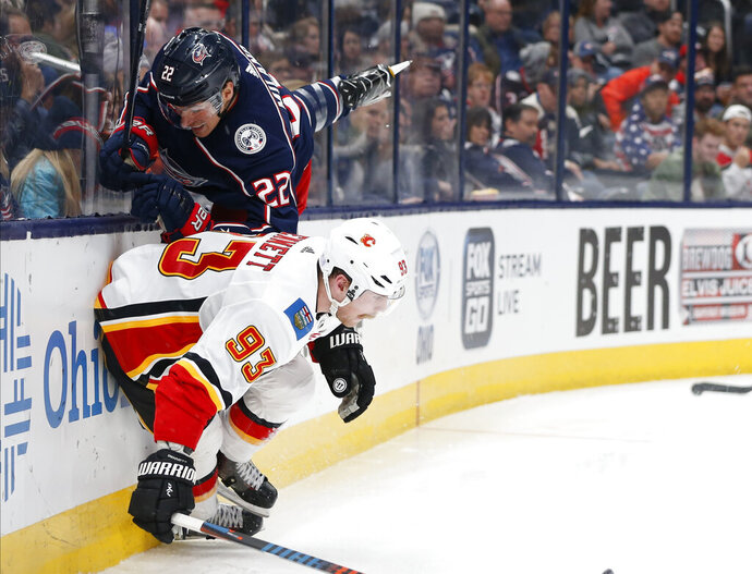 Calgary Flames' Sam Bennett, bottom, checks Columbus Blue Jackets' Sonny Milano during the third period of an NHL hockey game Saturday, Nov. 2, 2019, in Columbus, Ohio. (AP Photo/Jay LaPrete)