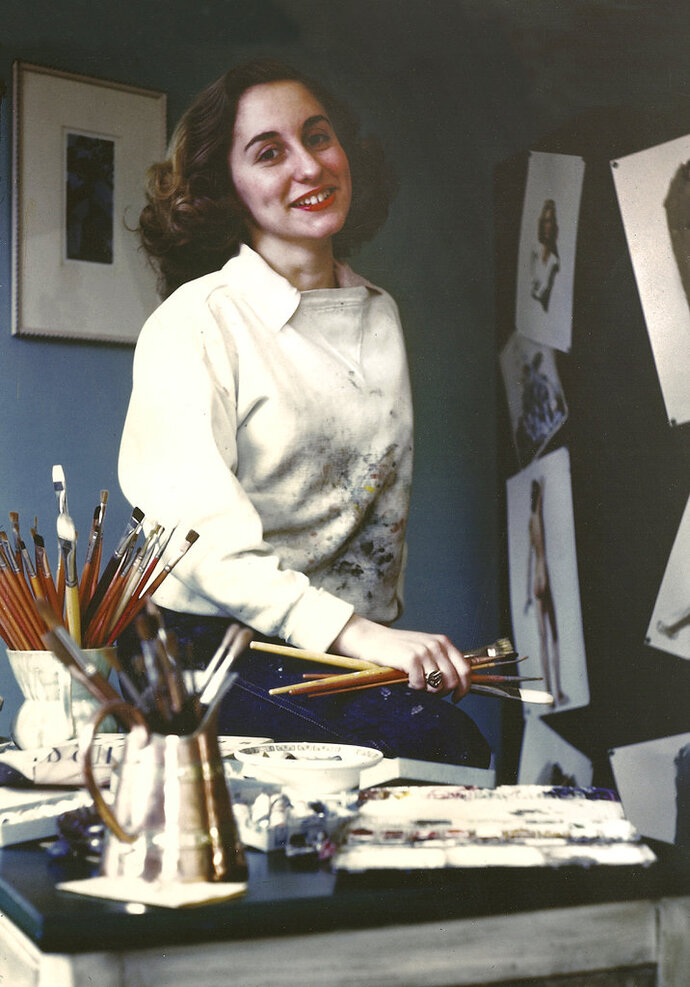 In this 1945 photo provided by the Norman Rockwell Museum, artist Gloria Stoll Karn poses in her New York studio. Karn, a pioneering artist, who had a brief but productive stint as an illustrator of pulp crime and romance magazines during the 1940s, is being celebrated with an exhibition of her works opening Saturday, Feb. 10, 2018 at the Norman Rockwell Museum in Stockbridge, Mass. (Norman Rockwell Museum via AP)