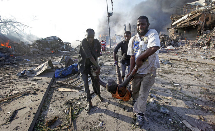 FILE - In this Saturday, Oct. 14, 2017 file photo, Somalis remove the body of a man killed in a huge explosion from a truck bomb that killed at least 20 people, in the capital Mogadishu, Somalia. U.N. experts said in a report circulated Tuesday, Nov. 12, 2019 that al-Shabab extremists in Somalia remain