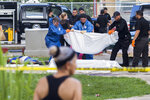 EDS NOTE: GRAPHIC CONTENT - Police investigators recover the bodies at the the scene of a multiple killing in San Juan, Puerto Rico, Tuesday, Oct. 15, 2019. Several people are reported dead following a shooting in the Rio Piedras neighborhood of San Juan. (AP Photo/Dennis M. Rivera Pichardo)