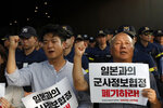 South Korean protesters shout slogans during a rally demanding the South Korean government to abolish the General Security of Military Information Agreement, or GSOMIA, an intelligence-sharing agreement between South Korea and Japan, in front of Japanese embassy in Seoul, South Korea, Thursday, Aug. 22, 2019. The letters read