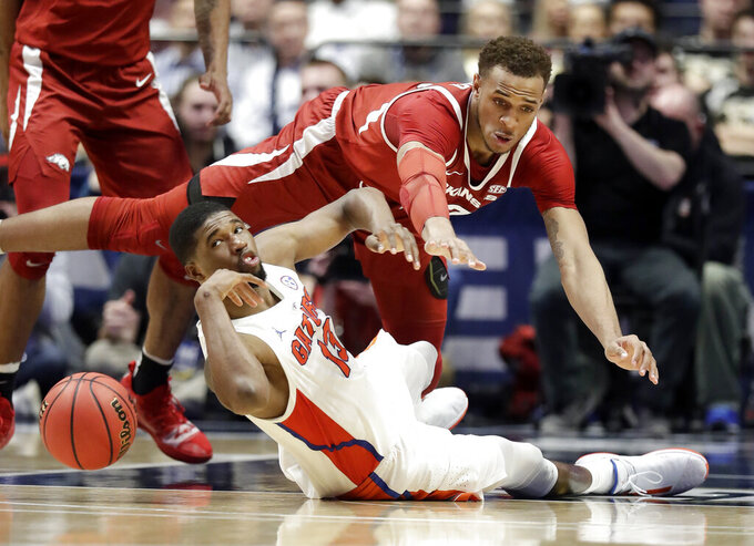 Florida's Kevarrius Hayes (13) and Arkansas's Daniel Gafford scramble for the ball in the second half of an NCAA college basketball game at the Southeastern Conference tournament Thursday, March 14, 2019, in Nashville, Tenn. Florida won 66-50. (AP Photo/Mark Humphrey)