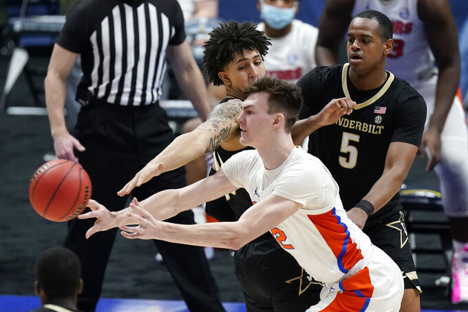Florida's Colin Castleton (12) passes the ball away from Vanderbilt defenders Myles Stute, top left, and D.J. Harvey (5) in the second half of an NCAA college basketball game in the Southeastern Conference Tournament Thursday, March 11, 2021, in Nashville, Tenn. (AP Photo/Mark Humphrey)