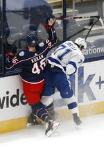Tampa Bay Lightning's Anthony Cirelli, right, checks Columbus Blue Jackets' Dean Kukan during the second period of an NHL hockey game Thursday, Jan. 21, 2021, in Columbus, Ohio. (AP Photo/Jay LaPrete)