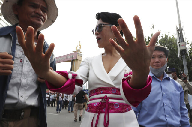 Theary Seng, center, a Cambodian-American lawyer gestures as she enters the Phnom Penh Municipal Court, in Phnom Penh, Cambodia, Thursday, Nov. 26, 2020. A Cambodian court on Thursday began hearing the cases of nearly 130 opponents and government critics charged with treason for taking part in nonviolent political activities over the past three years, in what one of them described as a sham trial. Theary Seng, who has long been one of the most outspoken critics of Hun Sen and his government, is one of the best known defendants living in Cambodia.(AP Photo/Heng Sinith)