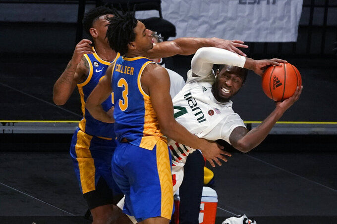 Miami guard Elijah Olaniyi, right, looks for an open teammate past Pittsburgh forward Noah Collier (3) and guard Au'diese Toney, rear, during the second half of an NCAA college basketball game, Wednesday, Dec. 16, 2020, in Coral Gables, Fla. (AP Photo/Wilfredo Lee)