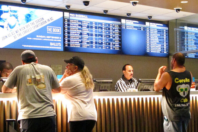 In this Sept. 5, 2019 photo, gamblers place sports bets at Bally's casino in Atlantic City, N.J. New Jersey gambling regulators have approved wagering on the XFL, becoming the sixth state to approve bets on the revived football league that last operated in 2001. Its season begins Feb. 8, 2020. (AP Photo/Wayne Parry)