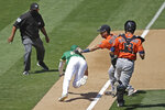 Houston Astros' Alex Bregman, second from right, tags out Oakland Athletics' Mark Canha during a rundown between third and home during the sixth inning of a baseball game Saturday, Aug. 8, 2020, in Oakland, Calif. (AP Photo/Ben Margot)