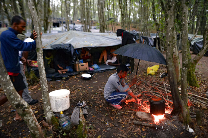 A migrant cooks on an open fire at a makeshift camp in a forest outside Velika Kladusa, Bosnia, Friday, Sept. 25, 2020.(AP Photo/Kemal Softic)