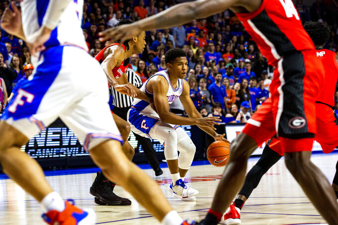 Florida guard Noah Locke, center, moves past multiple Georgia players during an NCAA college basketball game Saturday, March 2, 2019, in Gainesville, Fla. (Lauren Bacho/The Gainesville Sun via AP)