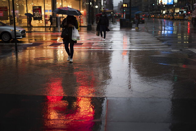 A shopper walks in a rainstorm, Monday, Nov. 30, 2020 in New York. With people staying home as virus cases surge, Cyber Monday is expected to be the biggest online shopping day yet, bringing in nearly $13 billion in one day. (AP Photo/Mark Lennihan)