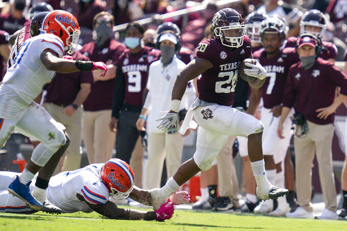 Texas A&M running back Isaiah Spiller (28) steps away from Florida linebacker Brenton Cox Jr. (1) during a run down the sideline during the second half of an NCAA college football game, Saturday, Oct. 10, 2020. in College Station, Texas. (AP Photo/Sam Craft)