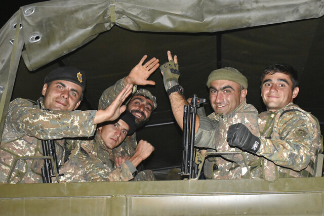 In this photo released on Tuesday, Oct. 6, 2020, Armenian soldiers wave to a photographer as they sit in a truck during fighting with Azerbaijan's forces in self-proclaimed Republic of Nagorno-Karabakh, Azerbaijan, Sunday, Oct. 4, 2020. The clashes have continued despite numerous international calls for a cease-fire. (Press office of Armenian Defense Ministry PAN Photo via AP)