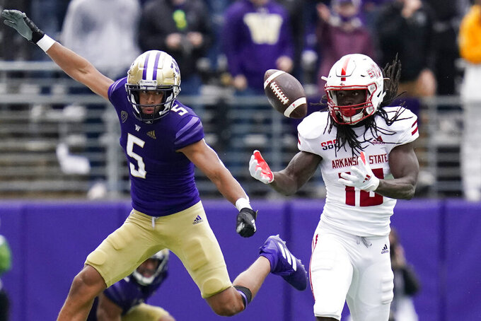 Arkansas State's Te'Vailance Hunt, right, can't catch a pass thrown his way as Washington's Alex Cook defends in the second half of an NCAA college football game, Saturday, Sept. 18, 2021, in Seattle. (AP Photo/Elaine Thompson)