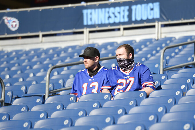 Two Buffalo Bills fans watch as players warm up before an NFL football game against the Tennessee Titans Tuesday, Oct. 13, 2020, in Nashville, Tenn. The game is the first this season where a limited number of fans are allowed into Nissan Stadium for a Titans game. (AP Photo/Mark Zaleski)