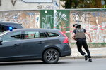 Police officer runs on a road in Halle, Germany, Wednesday, Oct. 9, 2019. One or more gunmen fired several shots on Wednesday in the German city of Halle. Police say a person has been arrested after a shooting that left two people dead. (Sebastian Willnow/dpa via AP)