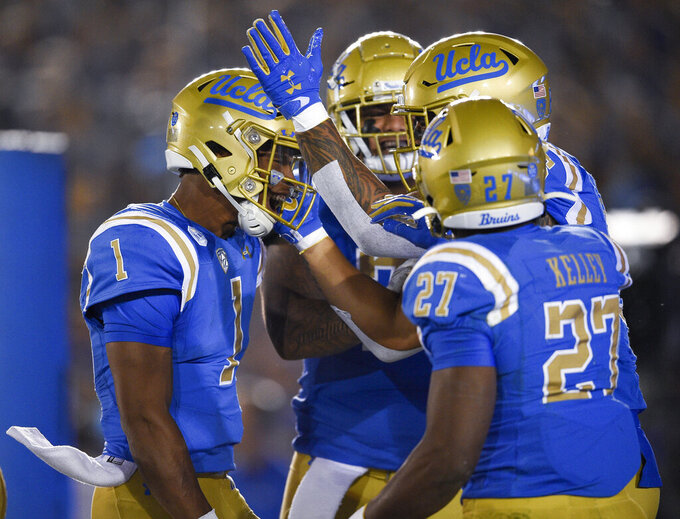 UCLA quarterback Dorian Thompson-Robinson, left, celebrates after throwing a touchdown pass to Devin Asiasi as Joshua Kelley, front, looks during the first half of an NCAA college football game against Colorado in Los Angeles, Saturday, Nov. 2, 2019. (AP Photo/Kelvin Kuo)