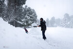 Morgan Baggs shovels the driveway at his home in Flagstaff, Arizona, on Thursday, Feb. 21, 2019. Schools across northern Arizona canceled classes and some government offices decided to close amid a winter storm that's expected to dump heavy snow in the region. (AP Photo/Felicia Fonseca)