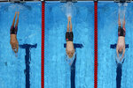 From left, France's Mewen Tomac, China's Xu Jiayu and United States' Joseph Armstrong compete in a 100-meter backstroke heat at the 2020 Summer Olympics, Sunday, July 25, 2021, in Tokyo. (AP Photo/David J. Phillip)