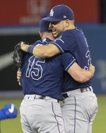 Tampa Bay Rays' Nate Lowe, right, and relief pitcher Emilio Pagan (15) celebrate on the field after they defeated the Toronto Blue Jays and clinched an American League wild-card berth in Toronto, Friday, Sept. 27, 2019. (Fred Thornhill/The Canadian Press via AP)