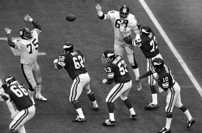 FILE - In this Jan. 12, 1975, file photo, Pittsburgh Steelers tackle Joe Greene (75) defends a pass as Minnesota Viking players Andy Maurer (66), Ed White (62), Mick Tingelhoff (53) and Ron Yary (73) protect quarterback Fran Tarkenton (10) during NFL football's Super Bowl IX at Tulane Stadium New Orleans, La. Tingelhoff, the ultimate ironman who started 240 consecutive games at a bruising position for the Minnesota Vikings and played in four Super Bowls, died, the Vikings and the Pro Football Hall of Fame announced, Saturday, Sept. 11, 2021. He was 81. (AP Photo/Harry Hall, File)