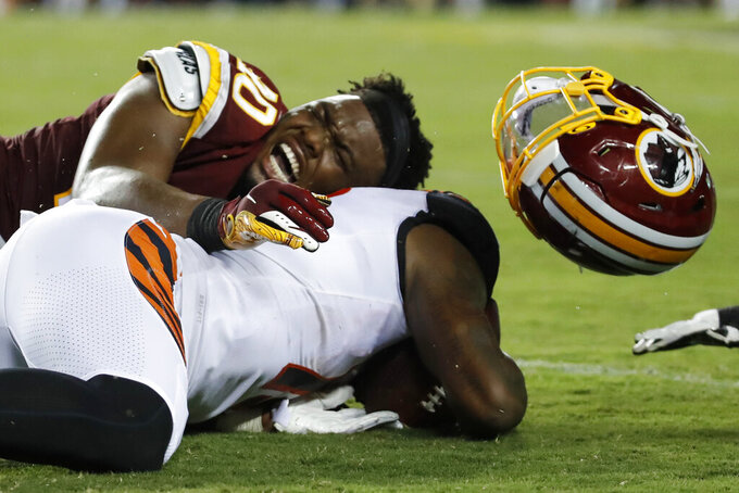 Washington Redskins linebacker Josh Harvey-Clemons (40) loses his helmet as he tackles Cincinnati Bengals wide receiver Auden Tate during the first half of an NFL preseason football game Thursday, Aug. 15, 2019, in Landover, Md. (AP Photo/Alex Brandon)