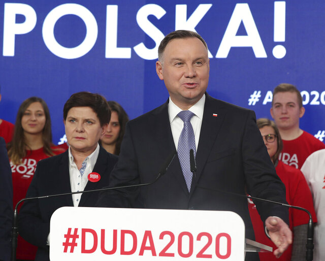 FILE - In this file photo taken Feb. 19, 2020, Poland's President Andrzej Duda, center, campaigning for his re-election in Warsaw, Poland.  The Polish government's determination to move forward with the May 10, presidential election during the coronavirus pandemic by making it an all-postal vote is creating anxiety and anger, and critics say the plan threatens public health and democracy in Poland.(AP Photo/Czarek Sokolowski)