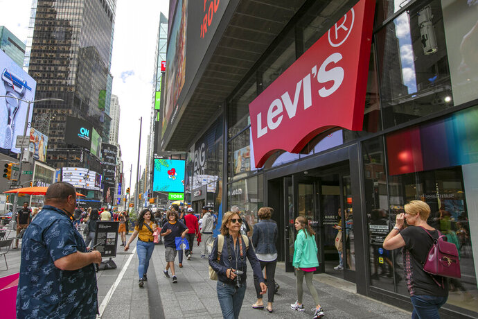FILE - In this June 14, 2019, file photo people pass the Levi's store in in New York's Times Square. Levi Strauss & Co. reports earns Tuesday, Oct. 8. (AP Photo/Richard Drew, File)